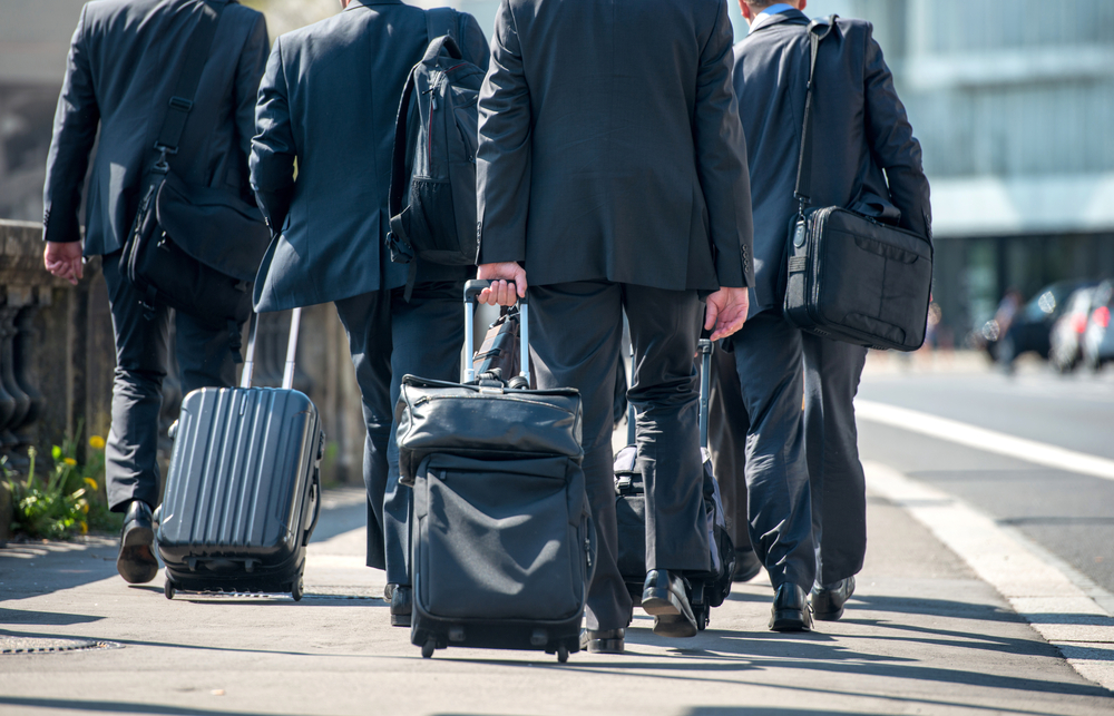 A group of businessmen pulling suitcases with luggage