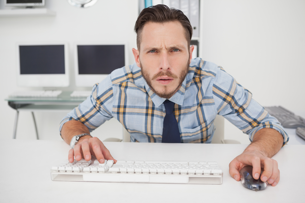 Focused casual businessman working at his desk in his office